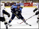 Toledo's Shane Berschbach, center, battles Wheeling's Harrison Ruopp for the puck during the Walleye's win on Friday.