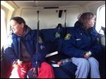 Sisters Leslie Roy, right, and Lee Marie Wright sit in a Michigan State Police helicopter after they were rescued Friday.