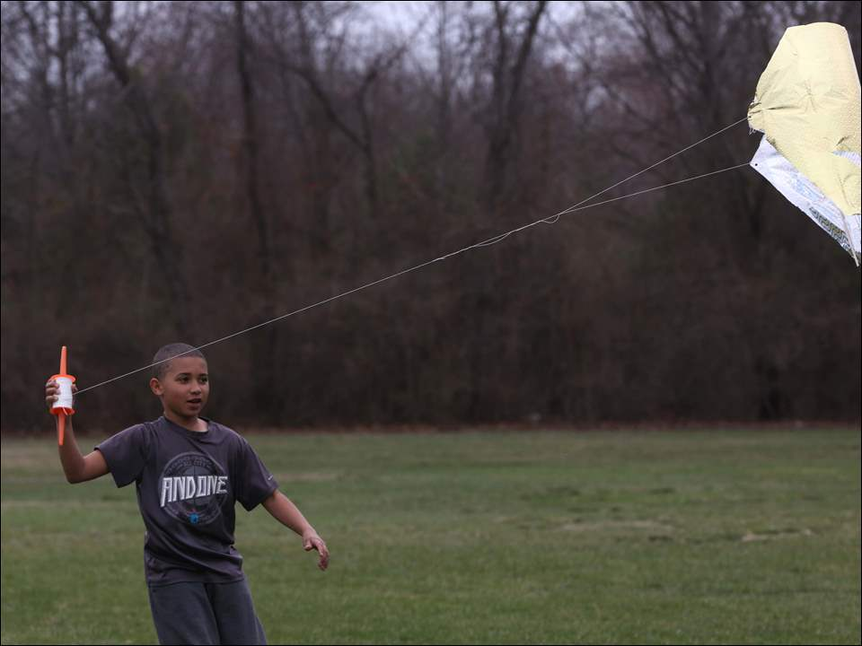 Travon Roberts, 11, gets his homemade kite off the ground.