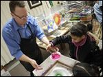 Glenwood Elementary School art teacher Jim Vasko helps second grader Nevia Bugg, 7, make a spin painting.