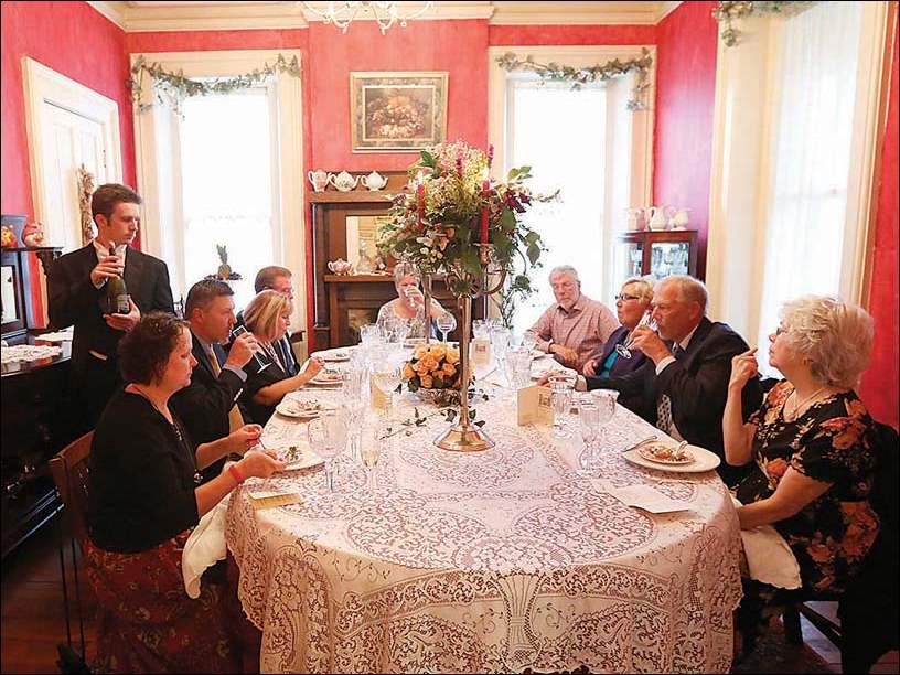 Wesley Flowers, left, serves wine during the annual Fourteen-Course Victorian Dinner: at the Matthew Brown House in the Vistula Historic District.