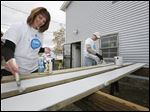 Kirsten Sebek and Jason Bartschy, both with Fifth Third Bank, paint boards that will be used to build raised beds for a community garden.  Fifth Third Bank is helping to build a large garden at the Sofia Quintero Arts & Cultural Center that will provide 10,000 pounds of food a year in Toledo. The effort is part of Fifth Third Banks' community service week.