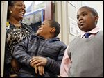 Counselor Shannon Tisdale jokes with Ronald Collins III, 8, center, and his cousin, Ryland Garrett, Jr., 10, at Martin Luther King, Jr. Academy on Monday.