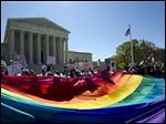 Demonstrators stand in front of a rainbow flag of the Supreme Court in Washington, today.