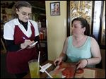 Donna Arp, left, who has been a waitress at Golden Lily since 1959, takes an order for Karen Ostrander, right, at the new Golden Lily Restaurant on April 15, 2015.