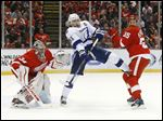 Tampa Bay center Steven Stamkos, center, battles for position as Detroit defenseman Niklas Kronwall defends with goalie Petr Mrazek in the first period on Monday night.