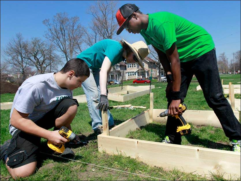 Seth Gerus, 14, left, and Breon Hill, 15, right, add stakes to a garden box during Global Youth Service Day at the Zepf Center.