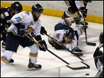 Toledo's Shane Berschbach (10) and Tyler Barnes reach for the puck during the third period.