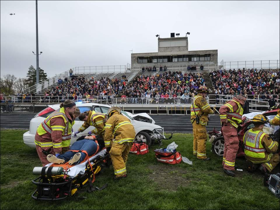 Maumee fire and police departments respond to a mock crash at Kazmaier Stadium at Maumee High School.
