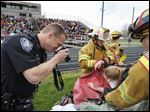 Maumee police officer Derek Sanderson photographs 'victim' Miranda Camp as Maumee firefighters Jim Dusseau, left, chief of the Fire Prevention Bureau, and Lt. Rich Ottensman tend to her during a mock crash at Kazmaier Stadium.