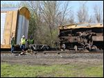 Railroad workers examine a derailed train car on a track at North Michigan Street near Albany Street in North Toledo.