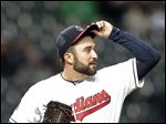Cleveland Indians starting pitcher T.J. House adjusts his cap in the fourth inning.