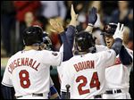Cleveland Indians' Brett Hayes, right, is congratulated by Lonnie Chisenhall, left to right, and Michael Bourn after Hayes hit a three-run home run.