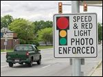 A signs warns motorists of an approaching traffic-enforcement camera near the intersection of Cherry Street and East Delaware Avenue in Toledo.