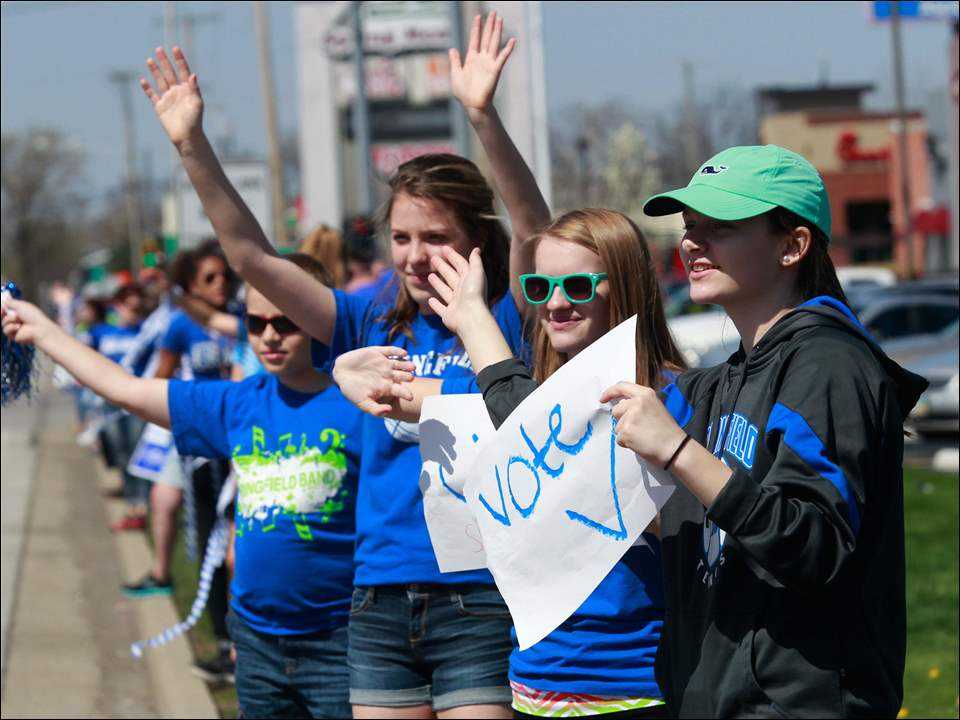 Students wave to motorists as part of a mile-long chain along Airport Highway in Holland of smiling Springfield Schools levy supporters.