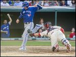 The Blue Jays' Josh Donaldson, left, evades a tag by Indians' catcher Roberto Perez to score on a two-run single by Jose Bautista in the sixth.