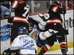 Toledo Walleye player Cody Lampl (32) gets sandwiched between Ft. Wayne Komets players Eric Faille (72) and Mike Embach (15)  during the third period on Saturday.