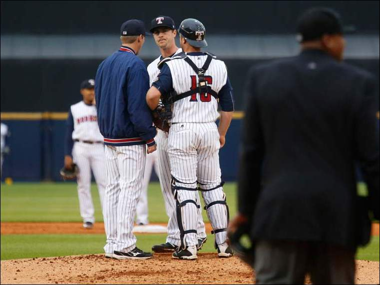 The umpire approaches the mound as Toledo pitching coach Mike Maroth, left, and catcher Bryan Holaday confer with starting pitcher Thad Weber.