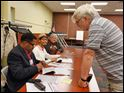 Anthony Medley, left, of Toledo, checks in voter Eric Waldhaus at the polling site at the Kent Branch of the Toledo-Lucas County Public Library. JaMalle Flournoy, second from left, and George Brown, both of Toledo, are also election officials.