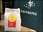 A bag of food from McDonald's ordered through the Postmates service sits next to a Postmates delivery bag during a delivery in New York today.