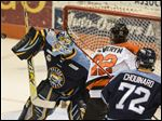 Toledo goalie Jeff Lerg, left, deflects the puck off his shoulder from the shot attempt by the Komets' C.J. Severyn during the second period.