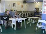 Election Official  smile as they operate a polling station inside a launderette in Oxford, England today.