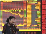 A Chinese woman is seen Tuesday near a display showing China's soaring stock index dip 4.06 percent at a brokerage house in Fuyang in central China's Anhui province.