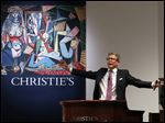 Auctioneer Jussi Pylkkanen takes bids on Pablo Picasso's Women of Algiers (Version O), which sold for nearly $179.4 million, making it set a world record for artwork at auction during a sale at Christie's Rockefeller Center in New York.