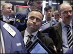 George Baskinger, center, works with fellow traders on the floor of the New York Stock Exchange on Tuesday.  U.S. stocks are opening lower following declines in European markets.