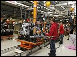 Employees work on the line where the Jeep Cherokee engine and its front suspension come together. Sales of the Cherokee, as well as the Jeep Wrangler, have skyrocketed this year.