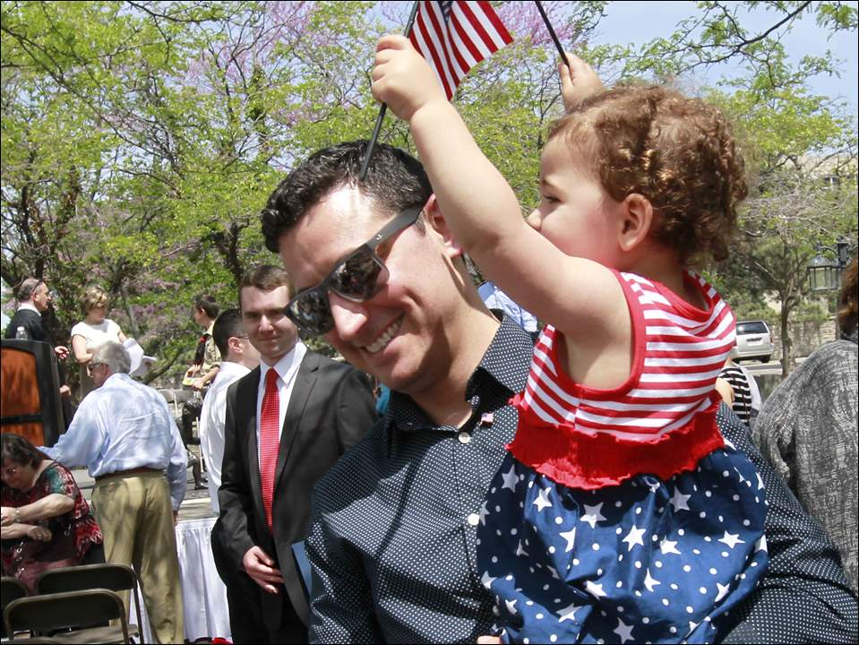 Gianni Vanni, formally of Italy, holds his daughter Gemma Vanni, 1.5, as she waves American flags after the Naturalization Ceremony at the Civic Center Mall in Toledo.