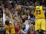 Cleveland Cavaliers forward LeBron James (23) blocks a shot by Chicago Bulls guard Derrick Rose (1) as Cavaliers guard Matthew Dellavedova (8) helps defend during the second half of Game 5 in a second-round NBA basketball playoff series Tuesday.