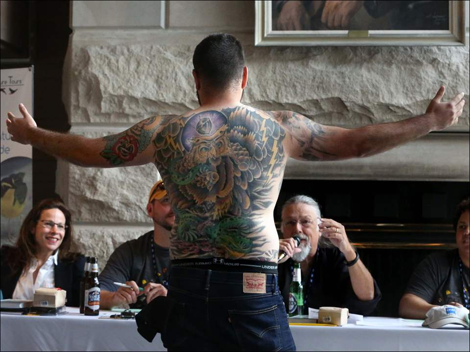 Jeremy Dominguez, of Beaver Creek, displays his Great Horned Owl tattoo to the crowd.