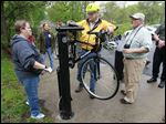 Keith Webb attaches a bike to a Fixit station at the McCord Road area of the University/Parks trail in Sylvania Township. Watching are Metropark employees Ruth Griffin, left, and Scott Carpenter, second from right. The service is a collaboration between the Metroparks and local bike companies.