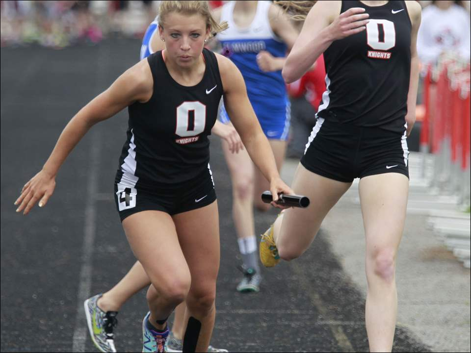Otsego's Alex Wenig takes the baton from Mallory Beach to win the girls 4x800 meter relay.