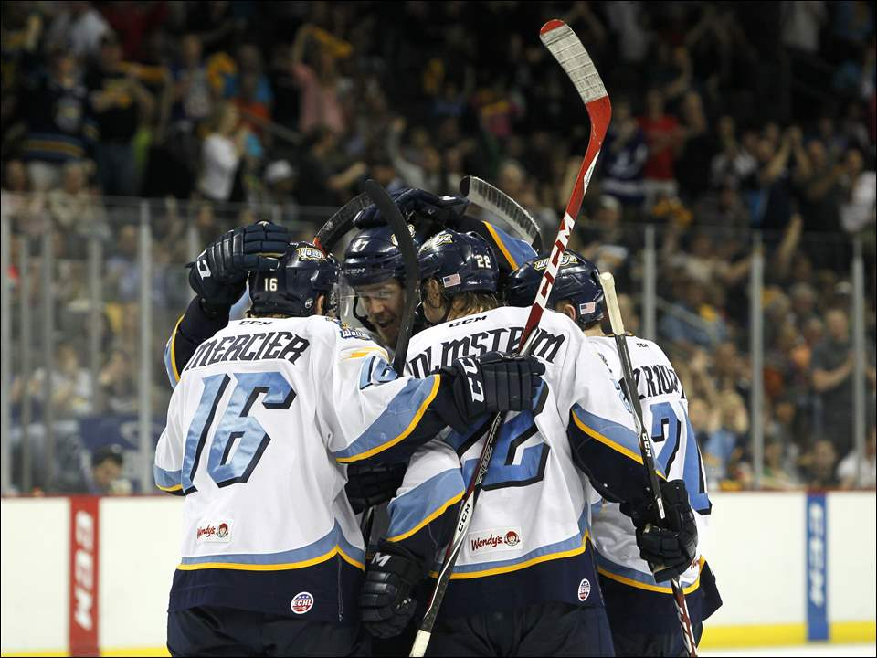 Walleye's A.J. Jenks, center, celebrates his third period goal with his team.