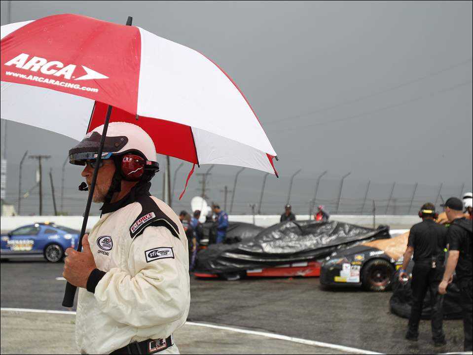 Official Dale Ingle walks with an umbrella during a rain delay at the ARCA Menards 200.