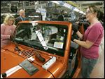 Amy Martinez, left, and Jill Opial, install parts in a Jeep Wrangler at Chrysler's Toledo Assembly Complex in Toledo.