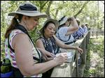 Geneva, Ohio resident Lydia Mach, left, and Sue Hetterscheidt, of Plymouth, Mich., look up birds in a guide during Biggest Week in American Birding event at Magee Marsh in Oak Harbor,.