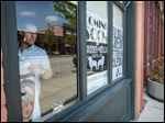 Rich Jambor, who owns Maddie & Bella Coffee Co., hangs signs at his coffee shop in the former Downtown Latte location.