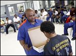 An inmate holds a box as a young man looks inside during a Youth Deterrent Program event at the Detroit Reentry Center  in this 2013 photo. The box held only a mirror. 'If you don't like what you see when you look in there,' the inmate told the young man, 'imagine what other people are seeing.'
