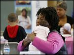 Christal Lawry holds her granddaughter Serenity Grace Lawry at a community baby shower at the Mayores Senior Center. The baby's mother was listening to a presentation.