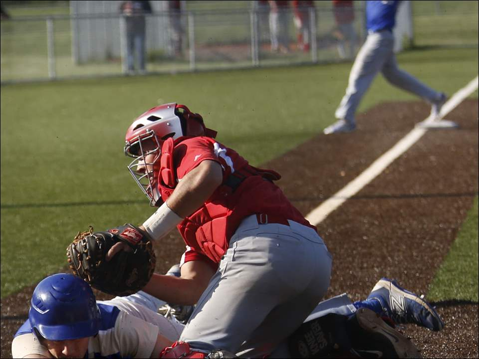 Findlay's Payton Evans is tagged out at the plate by Central Catholic catcher Colin Kaucher.