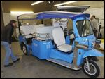 A worker checks a Tuk Tuk being prepared for export at eTuk USA in Denver, where the vehicle can be spotted downtown.