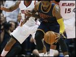 Cleveland Cavaliers guard Kyrie Irving (2) moves the ball as Atlanta Hawks guard Jeff Teague (0) looks on during the first half in Game 1 of the Eastern Conference finals of the NBA basketball playoffs, Wednesday in Atlanta.