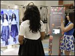 Sales manager Alysa Stefani, right, demonstrates the Memory Mirror for co-worker Porsche Colbert at the Neiman Marcus store in San Francisco. The mirror is outfitted with sensors, setting off motion-triggered changes of clothing. The mirror also doubles as a video camera, capturing a 360 degree view of what an outfit looks like and making side-by-side comparisons.