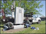 Ed Bond, left,  and Jeff Pettit of Artistic Memorials Ltd. install a monument Friday at Fort Meigs  in honor of  men from Virginia who served at the fort in the War of 1812.