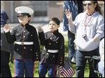 Gabriel Cepeda, 9, left, and his brother Frankie Cepeda, 7, with their mom, Rosie Cepeda, all of Toledo, wave to participants in the Memorial Day parade along Jackson Street near the grandstand.