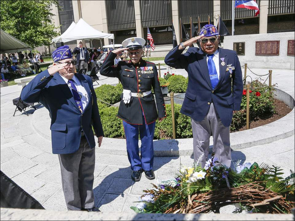 Members of the military Order of the Purple Heart salute after placing a wreath at the memorial in the Civic Center Mall during the Memorial Day parade in Toledo, Ohio on May 23, 2015. After the parade, a commemorative service was held as part of the day's events.