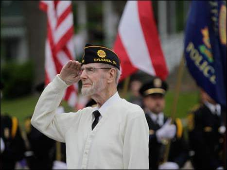 Veteran and American Legion member Clark Reber salutes during the brief ceremony at Ten Mile Creek at the start of the Sylvania Memorial Day parade.